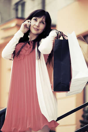 Fashion woman with shopping bags calling on mobile phone photo