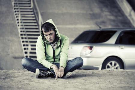 sitting on the ground: Sad young fashion boy sitting on the ground