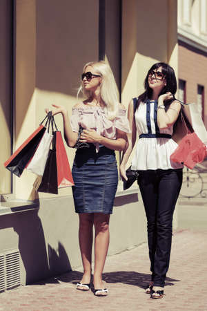 Two young fashion women with shopping bags at the mall photo