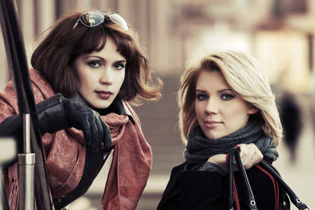 Two happy young fashion women on a city street photo