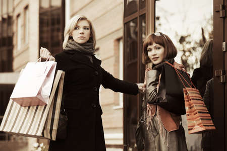 Two young fashion women with shopping bags photo