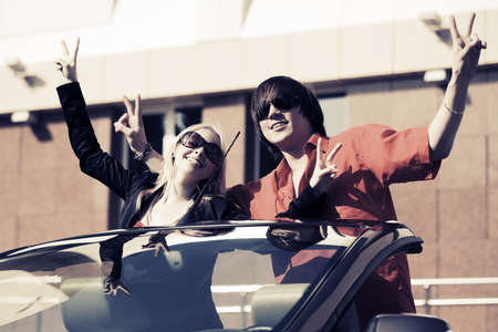 Happy young couple in a convertible car photo