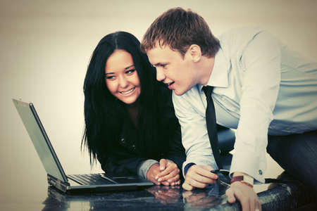 Young business couple using laptop outdoor photo