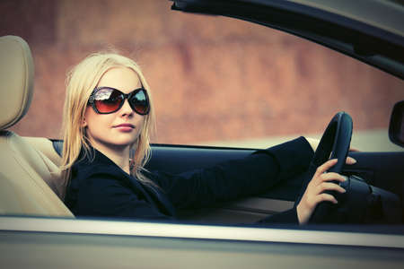 Young fashion woman in sunglasses driving convertible car photo