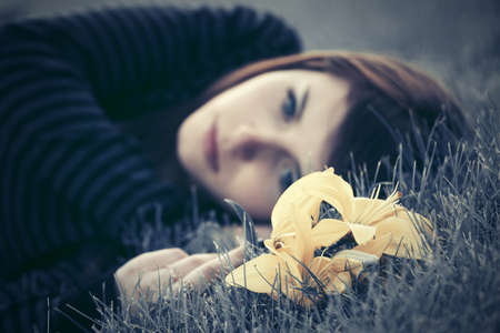 Sad young woman with a flowers lying on the grass photo