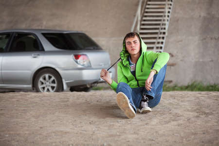 sitting on the ground: Sad young man in depression sitting on the ground next to his car