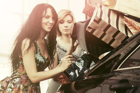 shopper: Two young women with shopping bags on the car parking Stock Photo