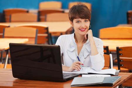 Junge Mode-Business-Frau mit Laptop am Bürgersteig Café