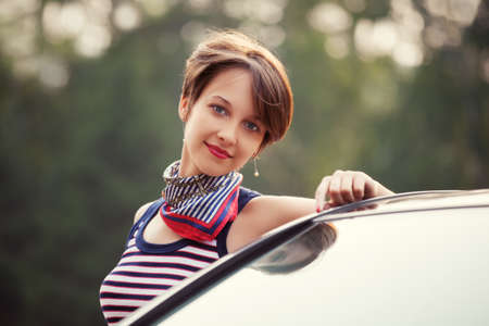 sleeveless top: Happy young fashion woman next to her car