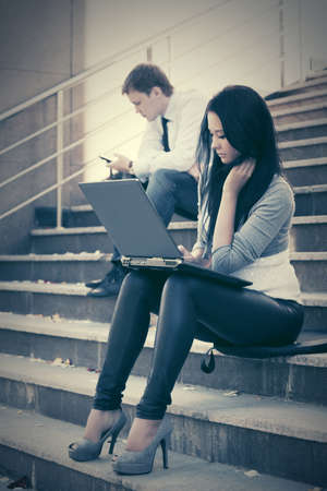 Young fashion business woman using laptop on the steps photo