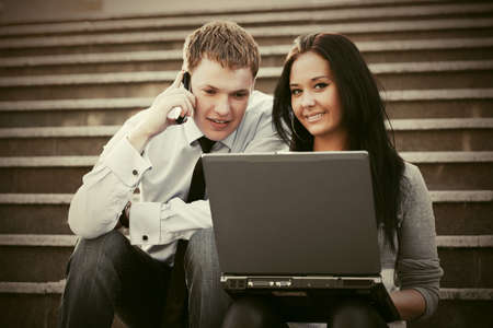 Young business man and woman with laptop on the steps photo