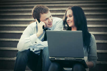 Young business couple with laptop on the steps photo