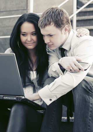 Young business couple using laptop on the steps photo