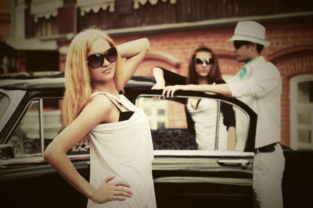 Happy young fashion blond woman in sunglasses next to retro car photo