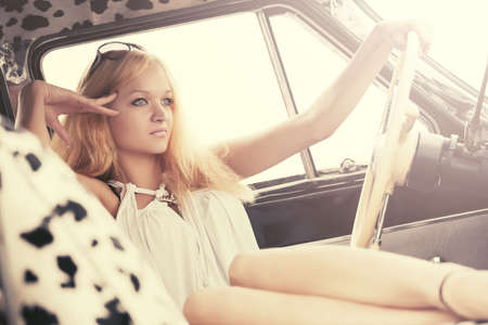 Young fashion blond woman relaxing in vintage car photo
