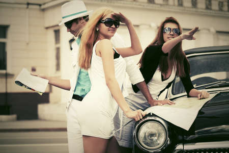 Young fashion people with a road map next to vintage car photo