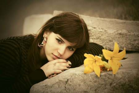 Sad young woman with a flowers lying on tombstone photo