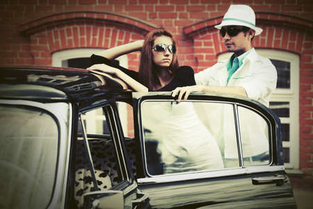Happy young fashion couple next to vintage car photo