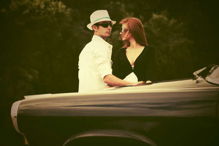 Young fashion couple in love next to vintage car photo