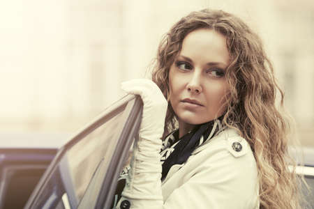 Sad beautiful fashion woman with long curly hairs next to her car photo
