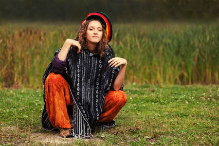 rasta hat: Young fashion hipster woman in rasta poncho sitting on the ground outdoor