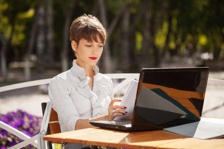 Young fashion business woman using laptop at sidewalk cafe photo