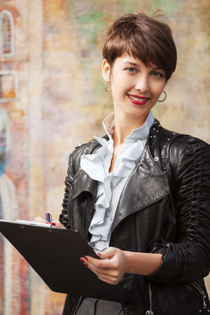 Happy young fashion business woman in leather jacket with clipboard photo
