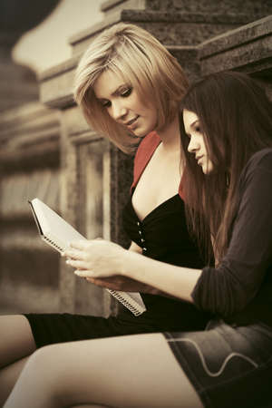 Two young fashion female students reading a notebook photo