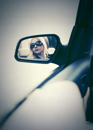 Blond woman in sunglasses looking in the car rear view mirror photo