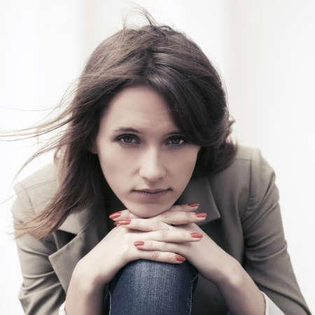Sad young fashion woman sitting on the city sidewalk