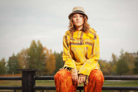 rasta hat: Young fashion hipster woman sitting on handrail outdoor