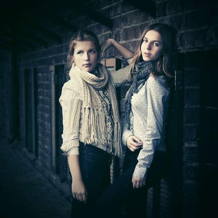 Two young fashion girls next to brick wall