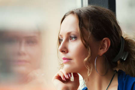 Sad young woman looking through window