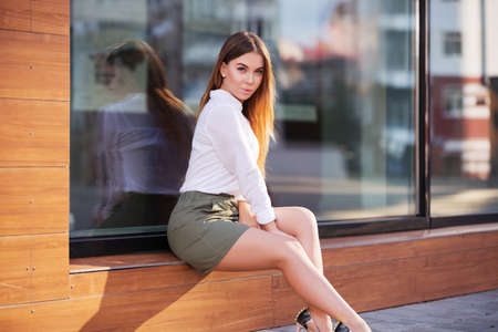 Young fashion woman sitting on the mall window in a city street. Stylish female model in white blouse and short skirt outdoor