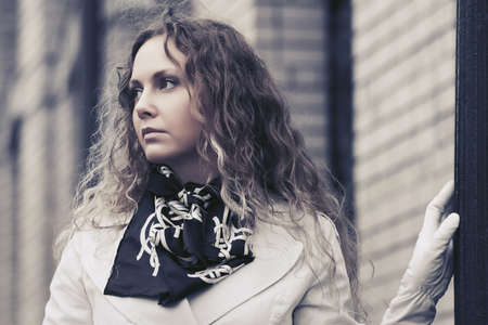 Beautiful fashion woman in white trench coat walking in city street. Stylish female model with long curly hairs outdoor