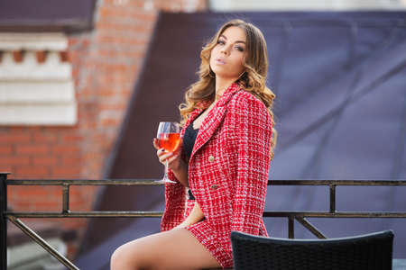 Young fashion woman with glass of wine at sidewalk cafe. Stylish female model in red tweed jacket and skirt suit  Foto de archivo