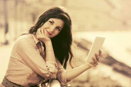 Young fashion woman using tablet computer outdoor Stock Photo