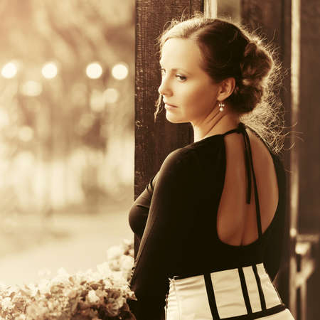 Sad beautiful fashion woman with bun updo hair wearing black blouse and white skirt standing on porch