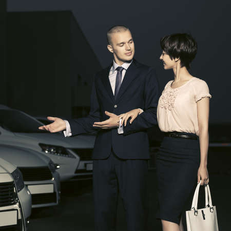 Young fashion business couple collecting new car at dealership lot Standard-Bild