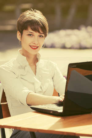 Young fashion business woman using laptop at sidewalk cafe Stylish female model in white shirt with pixie hair Stock Photo
