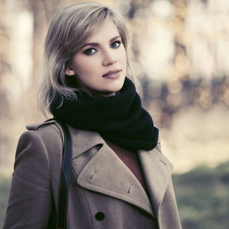 Happy young woman walking in autumn park Stylish blond fashion model wearing classic beige coat and black scarf 版權商用圖片