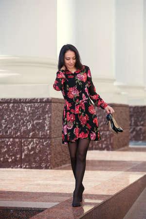 Happy young beautiful woman walking in city street Stylish fashion model wearing floral print dress