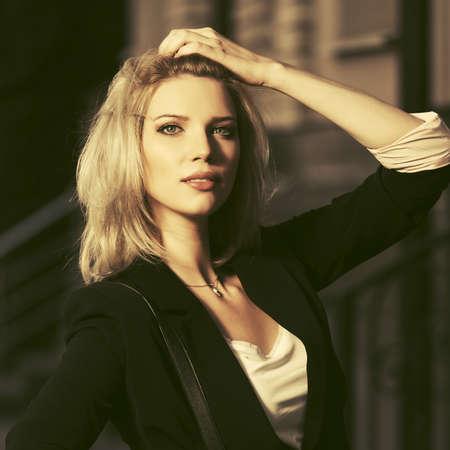 Young fashion blond business woman walking in city street  Stylish female model wearing black blazer