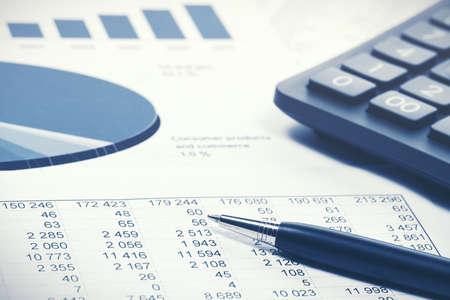 Financial accounting stock market graphs and charts. Pen and calculator on balance sheets Archivio Fotografico