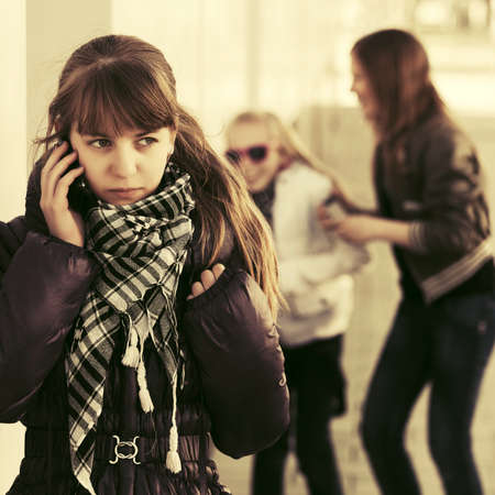 Teenage girl calling on cell phone on city street