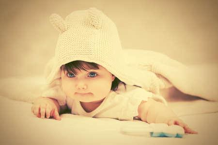 Baby girl in a hoodie sweatshirt crawling on blanket at home