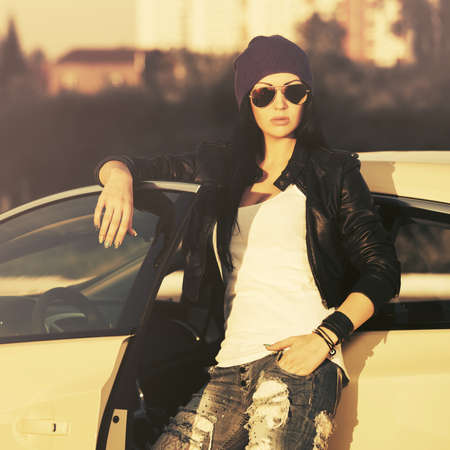 Young fashion hipster woman in sunglasses leaning on her car Stylish female model wearing black leather jacket and ripped jeans Фото со стока