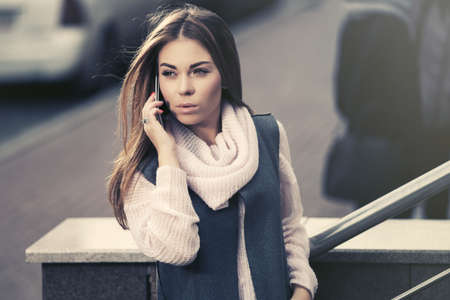 Young fashion woman calling on cell phone on city street Stylish female model wearing gray sleeveless coat and light pink sweater 写真素材