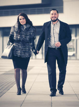 Happy young fashion couple in love walking on city street Stylish trendy man in classic black coat and woman wearing fox fur jacket