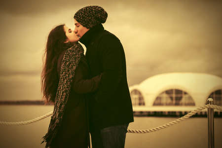 Happy young couple in love kissing outdoor  Stylish man and woman in classic coats beanie and scarf Фото со стока